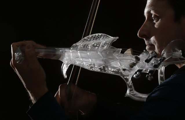 "French engineer and professional violinist Laurent Bernadac plays the ""3Dvarius"", a 3D printed violin made of transparent resin, during an interview with Reuters in Paris, France, September 11, 2015. (Photo by Christian Hartmann/Reuters)"