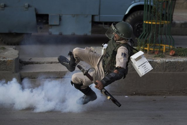 An Indian paramilitary soldier falls down as he tries to kick back an exploded tear gas shell thrown back at them by Kashmiri Muslim protesters at the end of a day long curfew in Srinagar, Indian controlled Kashmir, Monday, August 8, 2016. (Photo by Dar Yasin/AP Photo)