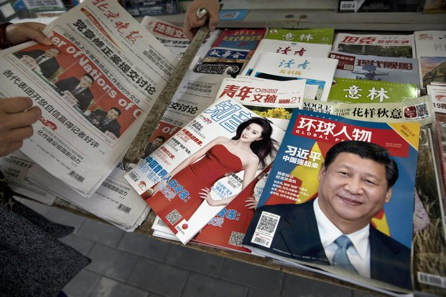 """In this Saturday, October 21, 2017 photo, a magazine featuring Chinese President Xi Jinping with the headline """"China becomes strong"""" is placed next to a magazine with popular Chinese actress Fan Bingbing at a news stand in Beijing, China. (Photo by Ng Han Guan/AP Photo)"""
