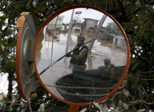 Japanese Self-Defence Force's 1st Infantry Regiment soldiers is seen on a boat are reflected on a traffic mirror as they conduct a search and rescue operation at a residential area flooded by the Kinugawa river, caused by Typhoon Etau at Araigi town in Joso, Ibaraki prefecture, Japan, September 12, 2015. (Photo by Issei Kato/Reuters)