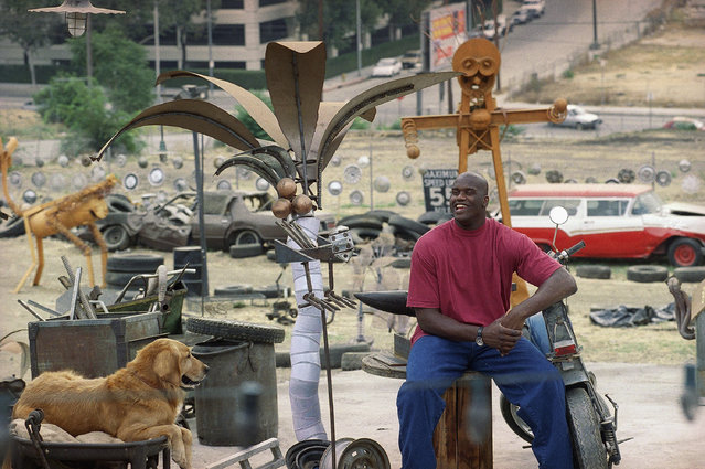 """Shaquille O'Neal smiles next to Clovis the dog, during the filming of the Warner Bros. film """"Steel"""" on a set made to look like a junkyard in downtown Los Angeles on Monday, September 16, 1996. O'Neal stars as the superhero Steel in the film which is due to be released in Oct. 1997. (Photo by Nick Ut/AP Photo)"""