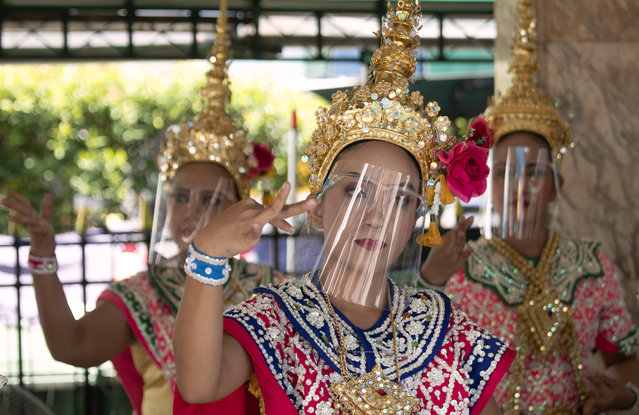 Thai classical dancers wearing face shield to help curb the spread of the coronavirus perform at the Erawan Shrine in Bangkok, Thailand, Thursday, May 28, 2020. Thai government continues to ease restrictions related to running business in capital Bangkok that were imposed weeks ago to combat the spread of COVID-19. (Photo by Sakchai Lalit/AP Photo)