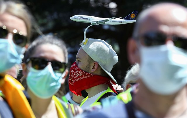 An employee of Lufthansa with a model plane attached to his head takes part in a protest against planned job cuts of Germany's flagship carrier due to the outbreak of the coronavirus disease (COVID-19), at the Lufthansa Aviation Centre in Frankfurt, Germany, June 24, 2020. (Photo by Ralph Orlowski/Reuters)