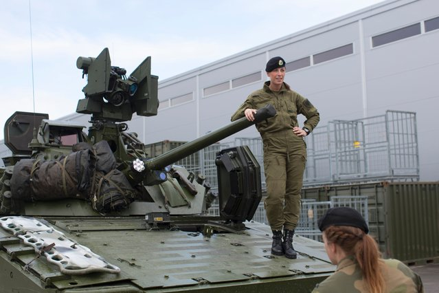 Female soldiers talk next to a CV90 combat vehicle at the armored battalion in Setermoen, northern Norway on August 11, 2016. (Photo by Kyrre Lien/AFP Photo)