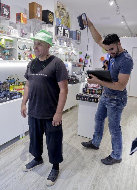 In this August 14, 2014 photo, Victor De Los Angeles, left, owner of Cubo toy store, demonstrates a Sense 3D scanner on coffee shop owner Kevin Micelli at his store in New York. (Photo by Julie Jacobson/AP Photo)