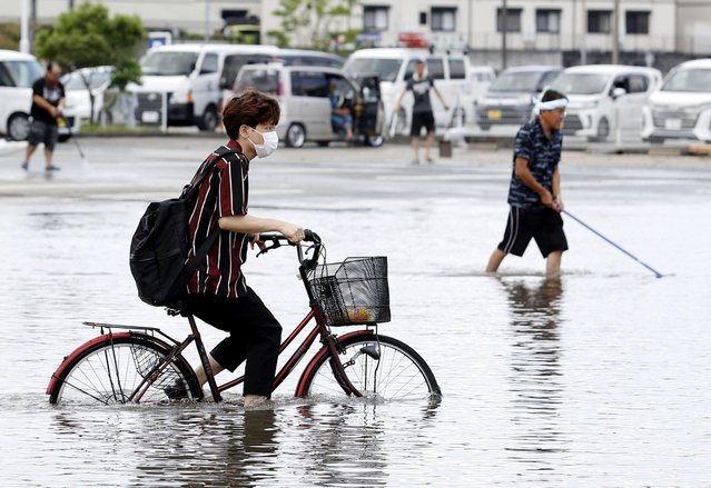 A man on a bicycle makes his way through a flooded road following heavy rains in Kurume, Fukuoka prefecture, southern Japan Wednesday, July 8, 2020. Floodwaters flowed down streets in southern Japanese towns hit by heavy rains. (Photo by Shoei Miyano/Kyodo News via AP Photo)