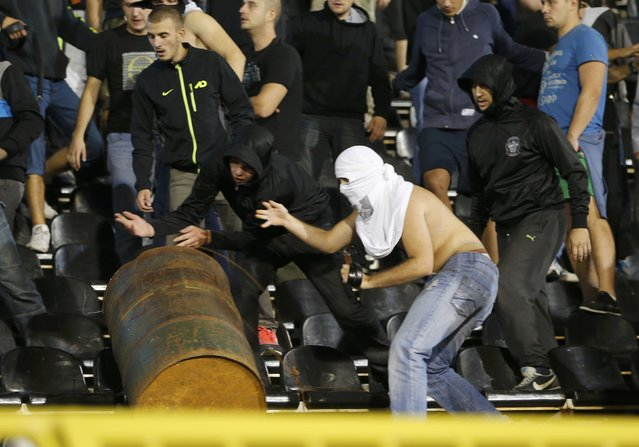 Fans of Serbia roll a barrel towards the riot police during clashes at the Euro 2016 Group I qualifying soccer match between Serbia and Albania at the FK Partizan stadium in Belgrade October 14, 2014. The politically-sensitive Euro 2016 qualifier between Serbia and Albania was abandoned on Tuesday following a brawl between players from both sides after a flag stunt. (Photo by Marko Djurica/Reuters)