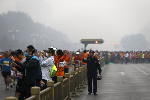 A traffic policeman asks runners, some are wearing masks to protect themselves from pollutants, to move along as others jog past Chang'an Avenue near Tiananmen Square shrouded in haze at the start of 2014 Beijing International Marathon in Beijing, China Sunday, October 19, 2014. (Photo by Andy Wong/AP Photo)