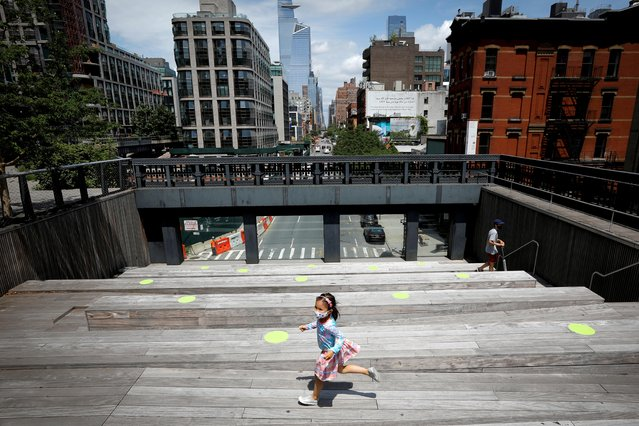 A child wearing a protective face mask plays on a sitting platform painted with social distancing circles on the elevated High Line Park in Manhattan on the first day of the park's re-opening in New York City, New York, July 16, 2020. (Photo by Mike Segar/Reuters)