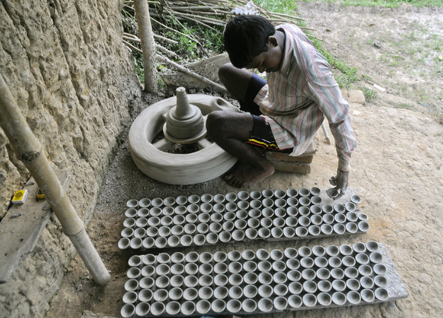 A potter makes clay lamps ahead of the Hindu festival of Diwali in Agartala, capital of Tripura, October 9, 2011. (Photo by Jayanta Dey/Reuters)