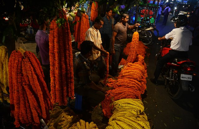 Indian flower sellers display garlands of marigolds to customers at a roadside stall ahead of the Hindu festival of Diwali in Siliguri on October 22, 2014. During Diwali, the Hindu festival of lights, people decorate their homes with flowers and light oil lamps in celebration of the festival which marks the homecoming of the god Lord Ram after vanquishing the demon King Ravana and returned to his kingdom Ayodhya. (Photo by Diptendu Dutta/AFP Photo)