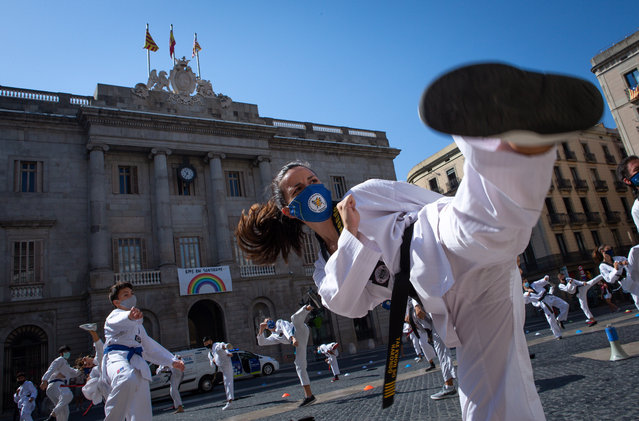 Dozens of people practice martial arts before the regional Government's headquarters in Barcelona, Spain, 27 July 2020, as a protest against the closure of gyms and martial arts centers in the region imposed by the Catalan Government due to a surge in coronavirus cases. (Photo by Enric Fontcuberta/EPA/EFE)