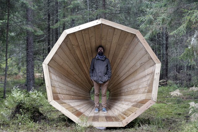 Head of the department of the interior architecture at Estonian Academy of Arts Hannes Praks poses for a picture in the wooden megaphone in the forest near Pahni village, Estonia, September 28, 2015. (Photo by Ints Kalnins/Reuters)