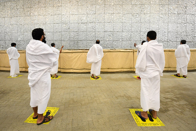 Muslim pilgrims cast stones at a pillar in the symbolic stoning of the devil, the last rite of the annual hajj, and the first day of Eid al-Adha, in Mina near the holy city of Mecca, Saudi Arabia, Friday, July 31, 2020. The global coronavirus pandemic has cast a shadow over every aspect of this year's pilgrimage, which last year drew 2.5 million Muslims from across the world to Mount Arafat, where the Prophet Muhammad delivered his final sermon nearly 1,400 years ago. Only a very limited number of pilgrims were allowed to take part in the hajj amid numerous restrictions to limit the potential spread of the coronavirus. (Photo by Saudi Ministry of Media via AFP Photo)