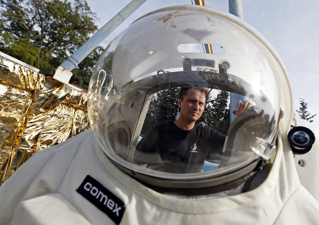 Comex Space division manager Peter Weiss checks the Gandolfi space suit before a training session in Marseille October 21, 2014. (Photo by Jean-Paul Pelissier/Reuters)