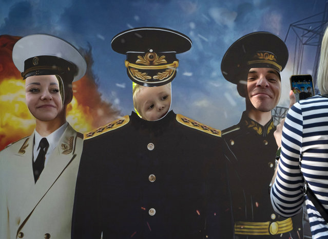 A family poses with their faces showing through a cardboard cutout depicting Russian Navy officers during the Navy Day celebration in St.Petersburg, Russia, Sunday, July 26, 2020. (Photo by Dmitri Lovetsky/AP Photo)