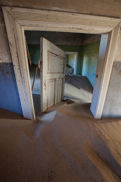 """Crooked Door in a Sand-filled Room"". The nearby dunes blow sand into Kolmanskop, a long-abadoned village for diamond mine workers. It's slowing being consumed by the surrounding landscape. Photo location: Kolmanskop; Namibia. (Photo and caption by Beverly Houwing/National Geographic Photo Contest)"