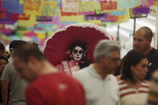 """A woman with her face painted as a skull attends the start of the """"Las Catrinas"""" festival,  ahead of the Day of the Dead in Cupula on the outskirts of Morelia , October 26, 2014. La Catrina is a popular figure in Mexico known as """"The Elegant Skull"""". The annual Day of the Dead is observed on November 1 and 2.  REUTERS/Alan Ortega (MEXICO - Tags: RELIGION SOCIETY TRAVEL)"""