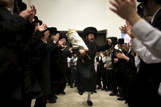 An ultra-Orthodox Jew dances with a Torah scroll during the celebrations of Simchat Torah in a synagogue at Mea Shearim neighbourhood of Jerusalem October 5, 2015. Jews around the world rejoice during the holiday, which marks the final reading of the Torah, and the renewal of the cycle for the coming year. (Photo by Ronen Zvulun/Reuters)