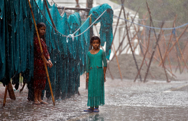 Girls stand in monsoon rains beside an open laundry in New Delhi, India, June 21, 2017. (Photo by Cathal McNaughton/Reuters)