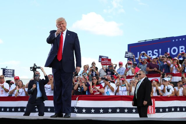 U.S. President Donald Trump gestures in front of supporters at Basler Flight Service in Oshkosh, Wisconsin, U.S., August 17, 2020. (Photo by Tom Brenner/Reuters)