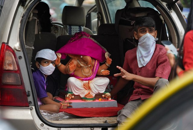 Children wearing protective face masks sit in the boot of a vehicle as they transport an idol of Hindu god Ganesh to their home on the first day of the ten-day-long Ganesh Chaturthi festival, amid the coronavirus disease (COVID-19) outbreak, in Mumbai, India on August 22, 2020. (Photo by Hemanshi Kamani/Reuters)