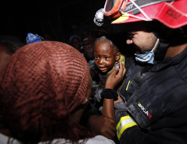 Two year old Redjeson Hausteen Claude reacts to his mother Daphnee Plaisin, after he is rescued from a collapsed home by Belgian and Spanish rescuers  in the aftermath of the powerful earthquake in Port-au-Prince, Thursday, January 14, 2010. (Photo by Gerald Herbert/AP Photo)