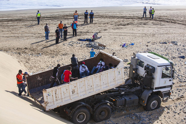 Would-be immigrants step into a truck on Maspalomas beach next to policemen on Gran Canaria in Spain's Canary Islands. (Photo by Borja Suarez/Reuters)