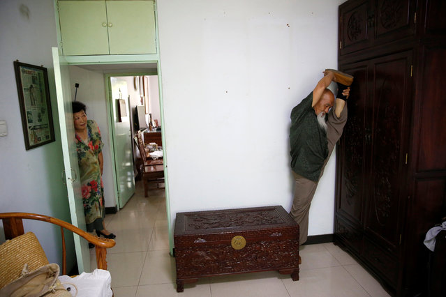 Kung Fu master Li Liangui while he demonstrates Suogugong Kung Fu skills for the camera as his wife Liang Xiaoyan watches him at his apartment in Beijing, China, July 2, 2016. (Photo by Kim Kyung-Hoon/Reuters)