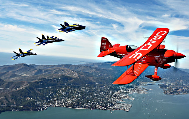 Team Oracle stunt pilot Sean Tucker (R) flies ahead of the U.S. Navy Blue Angels (L) as part of a practice run for Fleet Week over the bay in San Francisco, California on October 8, 2015. Fleet Week started on October 5 and goes till October 12 and will include ship tours and an air show. (Photo by Josh Edelson/AFP Photo)