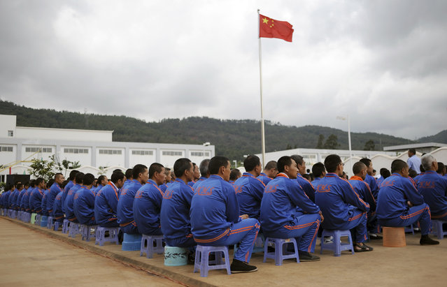 A Chinese national flag flies above male inmates as they watch a performance to mark the International Day against Drug Abuse and Illicit Trafficking at Kunming Municipal Compulsory Rehabilitation Centre in Yunnan province. (Photo by Wong Campion/Reuters)