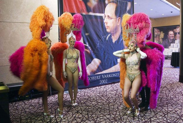A showgirl adjusts her costume before the 2014 World Series of Poker main event final table at the Rio hotel-casino in Las Vegas, Nevada November 10, 2014. The showgirls escorted players to the final table.The winner will take home a $10 million prize and a championship bracelet. (Photo by Steve Marcus/Reuters/Las Vegas Sun)