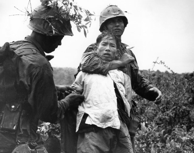 "A U.S. marine throttles a Viet Cong prisoner flushed from a rice paddy by marines advancing through the Viet an valley on December 15, 1965. The marines are supporting South Vietnamese troops in an effort to seal off escape routes for a communist regiment long entrenched in the valley that marines have dubbed ""Death Valley"". (Photo by AP Photo)"