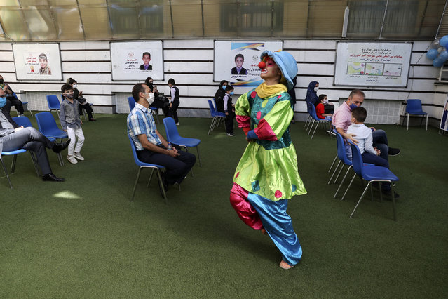 A clown performs as students and their parents wearing protective face masks to help prevent spread of the coronavirus attend the opening ceremony of the Hashtroudi school in Tehran, Iran, Saturday, September 5, 2020. Iran on Saturday opened the new school year after nearly seven months of closure as many expressed concern over a possible increase in infections of the Covid-19. (Photo by Vahid Salemi/AP Photo)