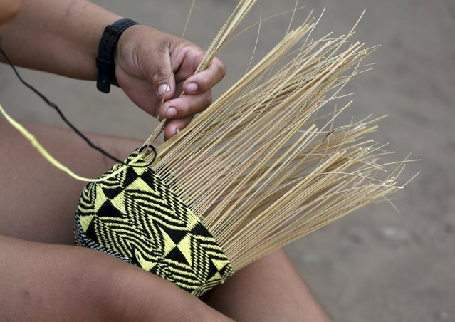 An Indigenous form the Kamayura tribe makes a handmade basket at the Xingu national park in Mato Grosso, Brazil, October 2, 2015. (Photo by Paulo Whitaker/Reuters)