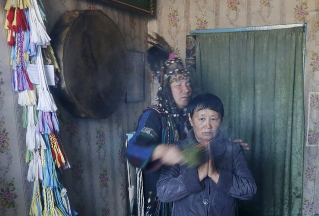 Yury Oorzhak (back), a shaman representing the so-called Adyg Eeren (Bear Spirit) society, conducts a session to clarify and predict the destiny of a customer, a local resident, at his residence in the town of Kyzyl, the administrative centre of Tuva region, Southern Siberia, Russia, October 7, 2015. (Photo by Ilya Naymushin/Reuters)
