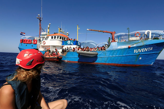 Ronia, 24, a member of the German NGO Jugend Rettet watches rescuers from the Save the Children NGO transferring migrants from the vessel Iuventa to their ship after her organisation rescued them from an overcrowded dinghy during an operation off the Libyan coast in the Mediterranean Sea September 21, 2016. (Photo by Zohra Bensemra/Reuters)