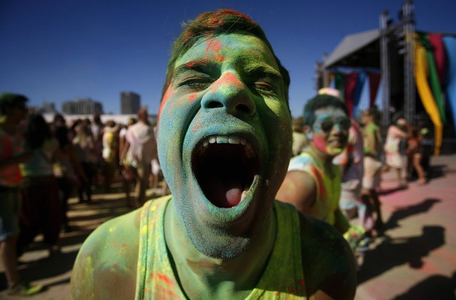 A reveller reacts as he is covered in coloured cornflour powder while participating in the Holi One festival in Cape Town, March 2, 2013. The event is inspired by the Hindu Holi spring festival of colour which originated in India. (Photo by Mark Wessels/Reuters)