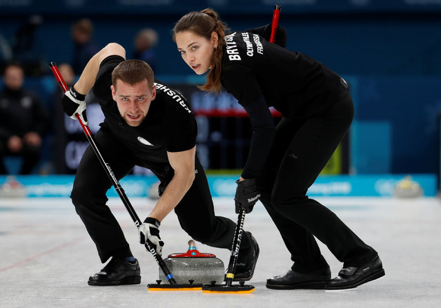 Olympic Athlete from Russia Anastasia Bryzgalova, left, sweeps the ice as teammate Aleksandr Krushelnitckii watches during a mixed doubles curling match against Canada' s Kaitlyn Lawes and John Morris at the 2018 Winter Olympics in Gangneung, South Korea, Saturday, February 10, 2018. (Photo by Cathal McNaughton/Reuters)