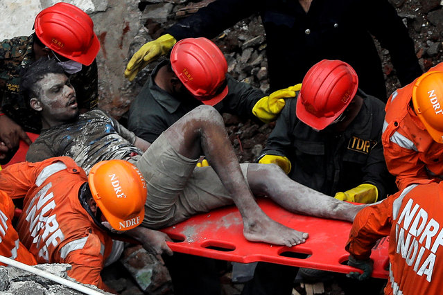 A man reacts on a stretcher upon being rescued by National Disaster Response Force (NDRF) officials from the debris of a three-storey residential building that collapsed in Bhiwandi on the outskirts of Mumbai, India, September 21, 2020. (Photo by Francis Mascarenhas/Reuters)