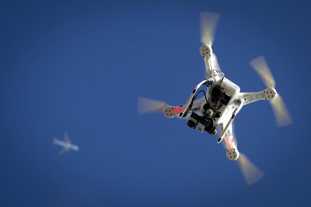 An airplane flies over a drone during the Polar Bear Plunge on Coney Island in Brooklyn, January 1, 2015. The Coney Island Polar Bear Club is one of the oldest winter bathing organizations in the United States and holds a New Year's Day plunge every year. (Photo by Carlo Allegri/Reuters)