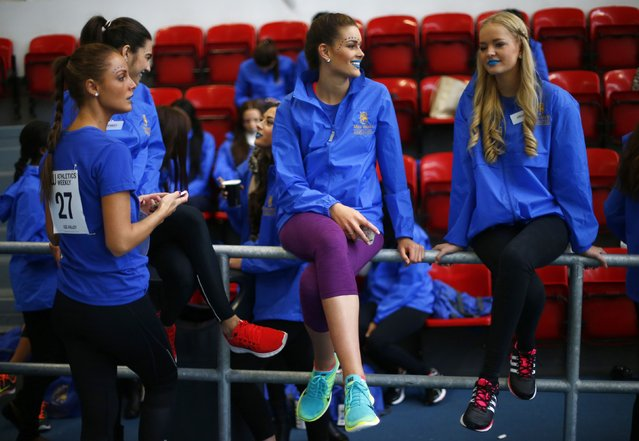 Competitors chat and check their phones during a break between events at  the Miss World sports competition at the Lee Valley sports complex in north London, November 26, 2014. (Photo by Andrew Winning/Reuters)