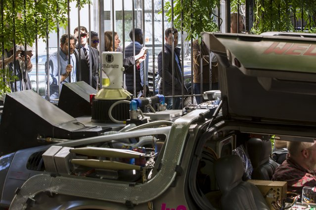 """Pedestrians stop to look at and photograph a DeLorean Motor Company DMC-12 customized to look identical to the car used in the film """"Back to the Future II"""" in New York, October 21, 2015. (Photo by Lucas Jackson/Reuters)"""