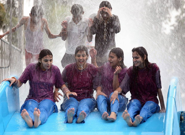 Young girls play in a water park to get respite from the humid and hot atmosphere in Bhopal, India, 07 June 2012. (Photo by Sanjeev Gupta/EPA)