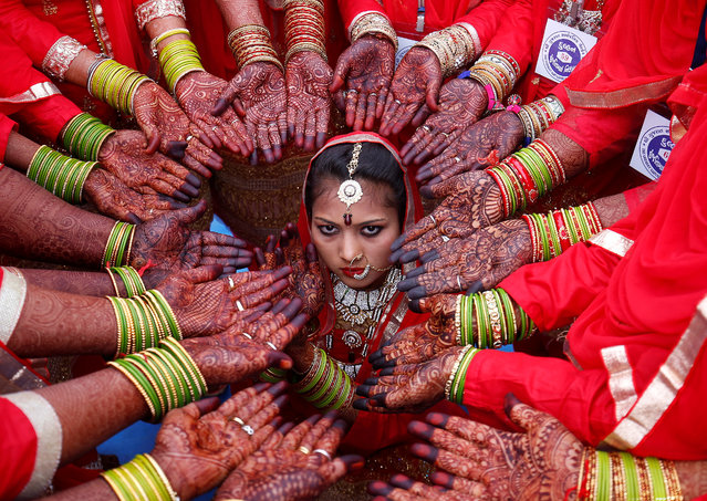 Brides display their hands decorated with henna around a bride as she poses for her own photographer during a mass marriage ceremony in which, according to its organizers, 70 Muslim couples took their wedding vows, in Ahmedabad, India, February 11, 2018. (Photo by Amit Dave/Reuters)