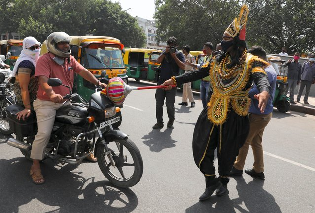 A volunteer of District Magistrate (DM) office dressed as Yamraj, or Hindu God of death, stops people for not wearing masks, amidst the spread of the coronavirus(COVID-19) disease, in New Delhi, India, September 28, 2020. (Photo by Anushree Fadnavis/Reuters)