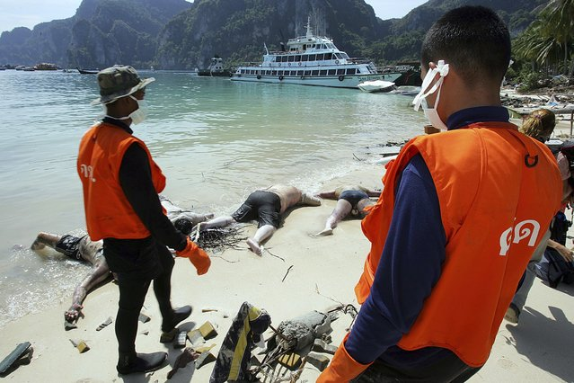 Rescue workers stand near dead bodies washed ashore in Ton Sai Bay in Thailand's Phi Phi island in this December 28, 2004 file photo. (Photo by Luis Enrique Ascui/Reuters)