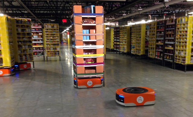 A Kiva robot drive unit is seen, foreground, before it moves under a stack of merchandise pods, seen on a tour of one of Amazon's newest distribution centers in Tracy, Calif., Sunday, November 30, 2014. This Amazon Fulfillment Center opened in 2013 and was refitted to use new robot technology in the summer of 2014. All year Amazon has been investing in ways to make shipping faster and easier to prepare for this holiday season. At this Northern California warehouse the company is employing robotics and other new technology to help workers process the annual onslaught of shopping orders. (Photo by Brandon Bailey/AP Photo)