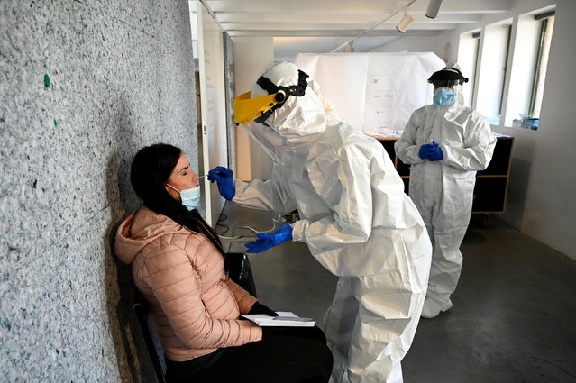 A healthcare worker collects a swab sample from a person at a coronavirus disease (COVID-19) test site during second round of mass nationwide testing at The New Synagogue arts centre in Zilina, Slovakia on November 7, 2020. (Photo by Radovan Stoklasa/Reuters)