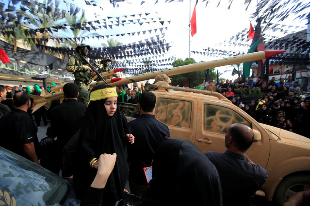 Hezbollah members drive a pick-up truck mounted with a mock rocket as they parade during a procession ahead of the day of Ashura, in the Saksakieh village, in southern Lebanon, October 9, 2016. (Photo by Ali Hashisho/Reuters)